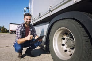Truck driver with thumbs up inspecting tires condition and checking pressure. Truck preparation before ride. Transportation services.