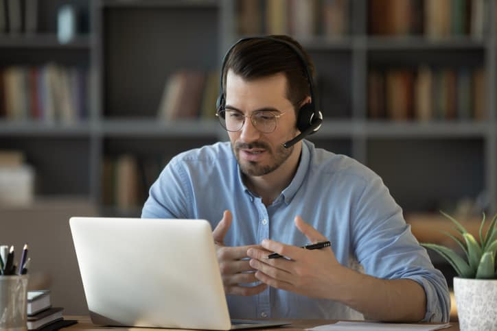 Confident man teacher coach wearing headset speaking, holding online lesson, focused student wearing glasses looking at laptop screen, studying, watching webinar training, listening to lecture