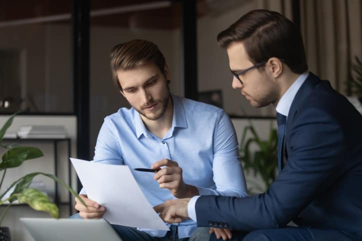 Focused young man employee holding paper document, discussing contract details or consulting about financial decision with smart ceo executive manager in formal wear, sitting together at modern office