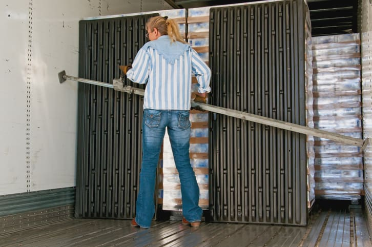 Pretty blonde woman placing a load-lock in the inside of a trailer to secure the loaded pallets during the upcoming trip.
