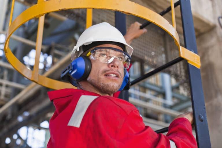Arbeitssicherheit_SiBe_Sicherheitsbeauftragter_Brandschutz_Worker climbing ladder at oil refinery